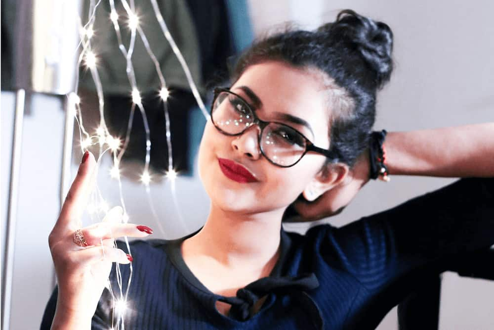 Girl with glasses holding fairy lights